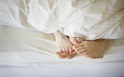 Young couple in bed, feet touching, allusion to female orgasm and fertility
