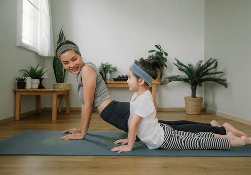 A mother doing yoga with her daughter