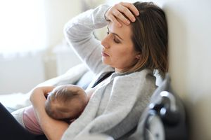Tired mother nursing baby daughter indoors at home, resting on bed