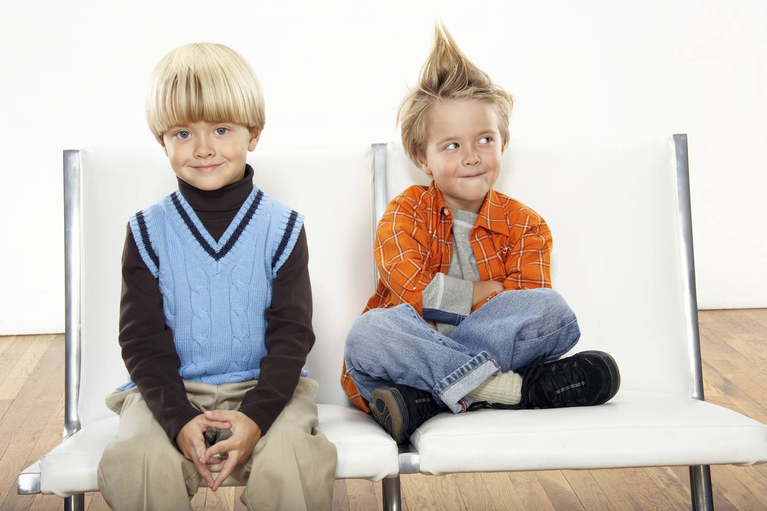 Twins sitting on chairs, wearing different styles
