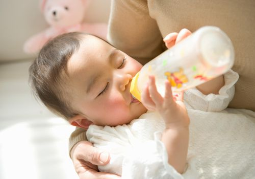 Mother holding daughter (6-9 months) drinking from bottle