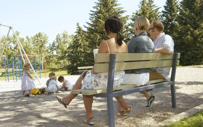 A picture of parents watching their children at a playground