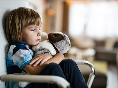 Sad boy embracing his teddy bear in home isolation.