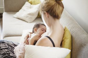 High angle view of mother breast feeding baby girl at home