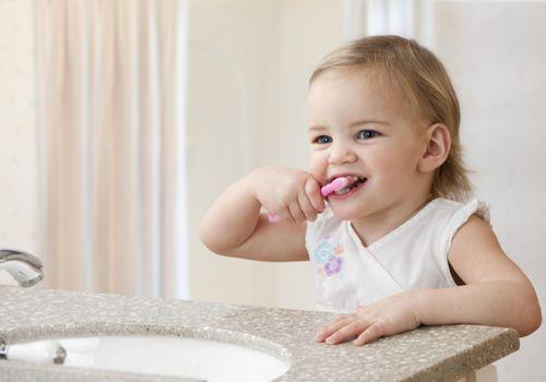 Toddler girl brushing teeth