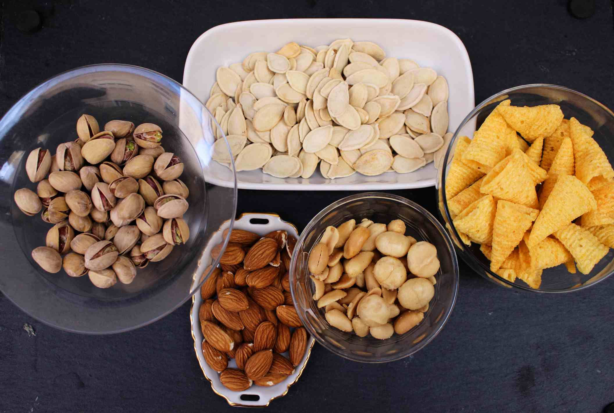 seeds, nuts and chips in small bowls