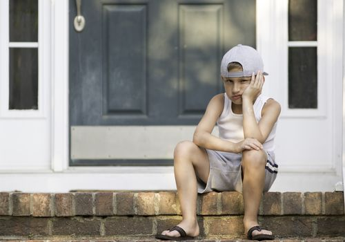 Upset boy sitting on the front step of his house