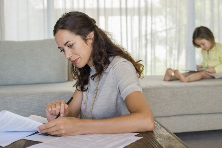 woman filling out paperwork with daughter in background