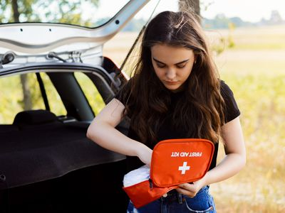 Young attractive girl stands near car with open back door and emergency lights is on, tries to find something in first aid kit