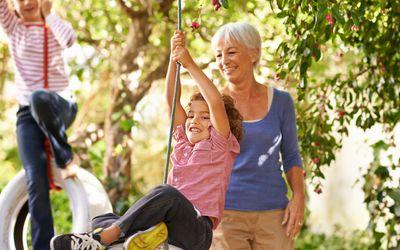 Grandparent helping grandkids on tire swings