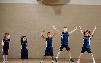 kids in gym doing jumping jacks