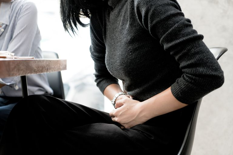 Asian woman has stomachache while she meeting with her friend in cafe.