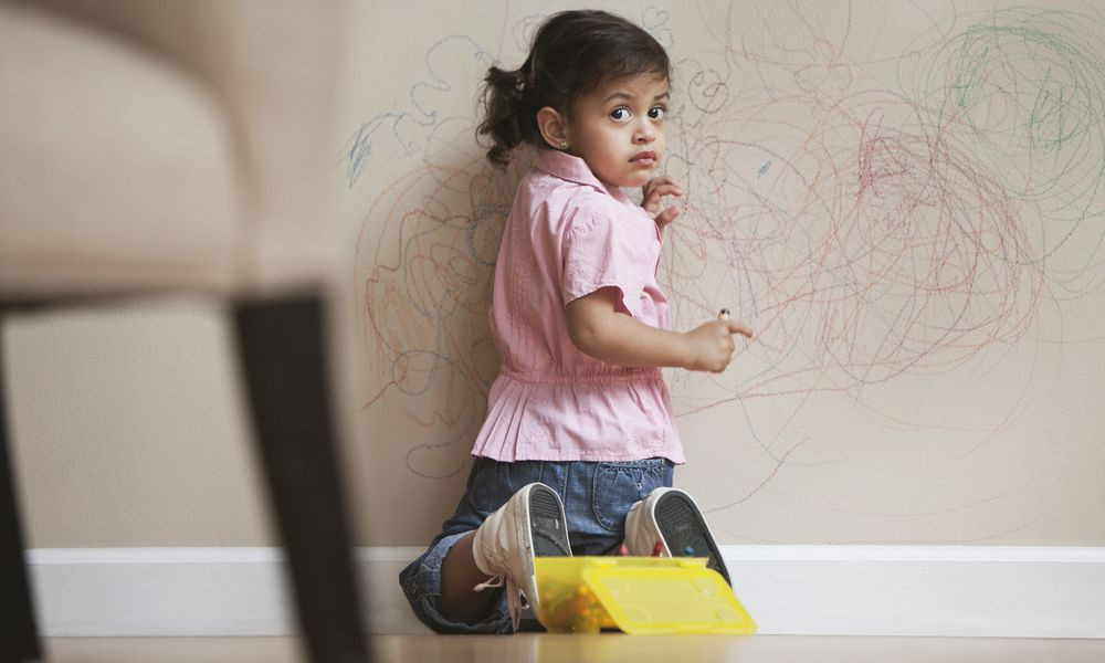 little girl drawing on the wall