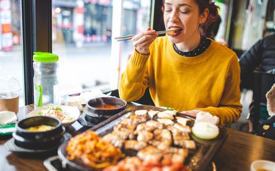 Woman eating at a Korean restaurant