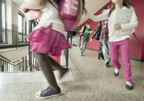 Elementary school students wearing backpacks, walking down a corridor