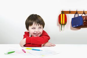 Laughing boy with drawings in classroom