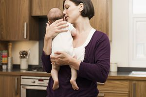 mother burping baby over shoulder in kitchen
