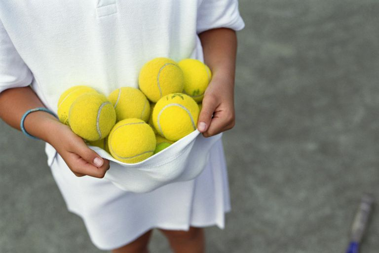 kid holding a bunch of tennis balls