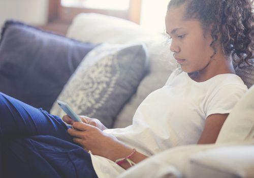 Upset teenager using her smartphone