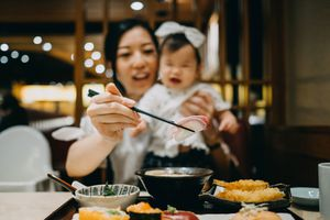Woman holding a baby while using chopsticks to pick up a piece of sushi