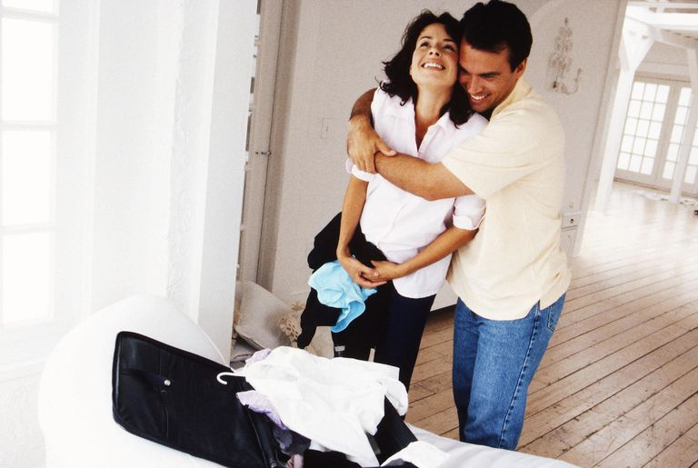 View of a man hugging his pregnant wife from behind and smiling.