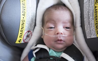 Premature baby in car seat getting oxygen