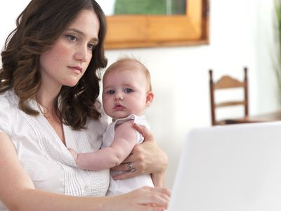 Mother looking up information on the computer with baby. Breastfeeding and Thrush, The Yeast Infection from Candida.