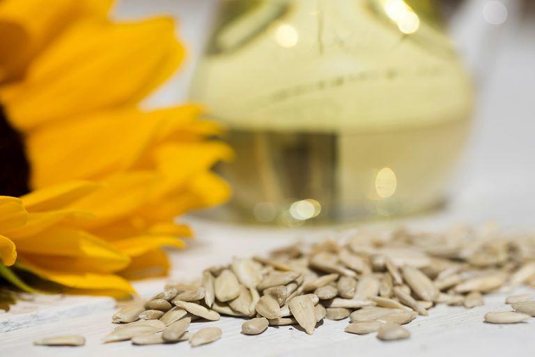 Sunflower seeds beside a sunflower and a glass jar of sunflower oil, a fertility superfood