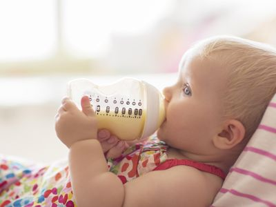 Baby girl drinking from bottle on sofa