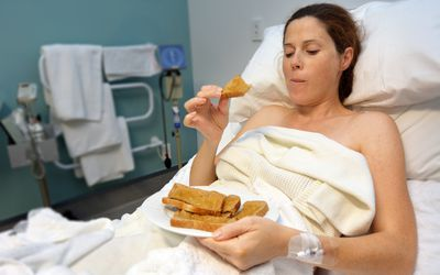 Pregnant woman eating peanut butter on toast in hospital delivery room