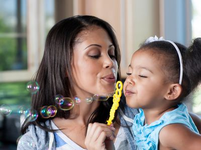Mother and young girl blowing bubbles