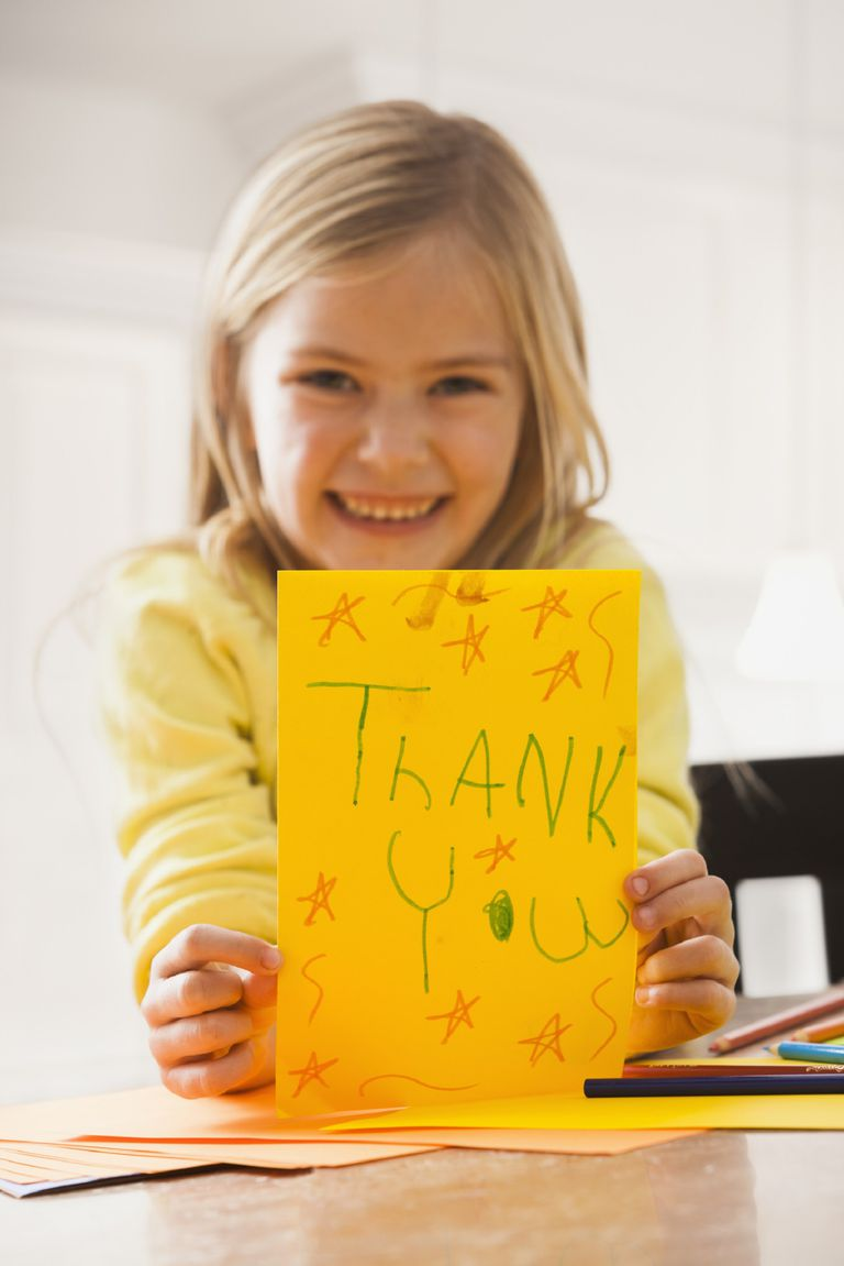 A picture of a child with a thank you card