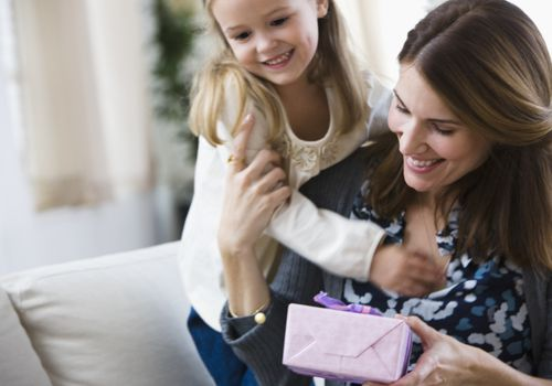girl giving a gift to her mother