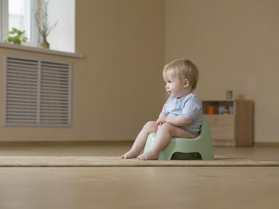 A happy toddler sitting on a potty chair, looking away