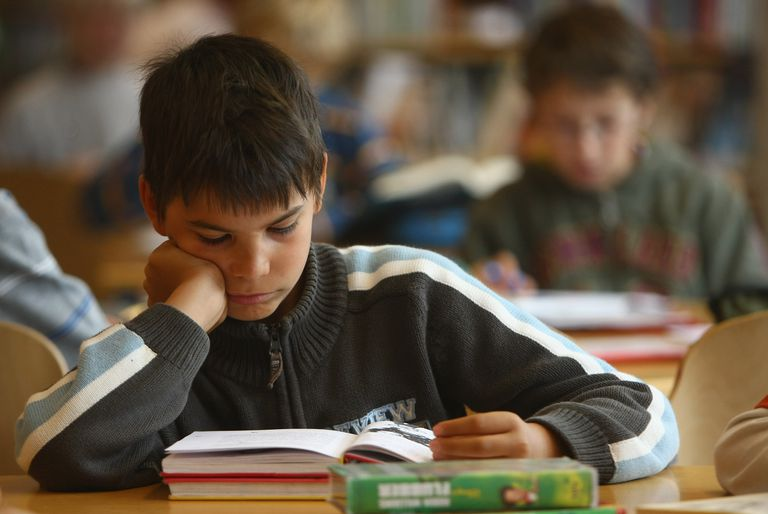 Young male student reading at classroom desk