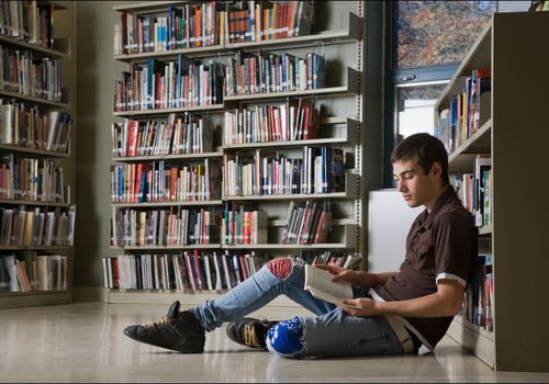 Teenage boy reading on the floor of a library