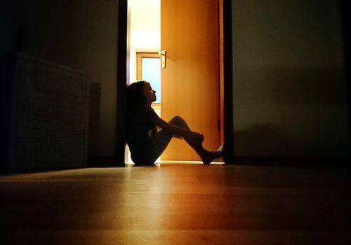 Child sitting in doorway of dark room