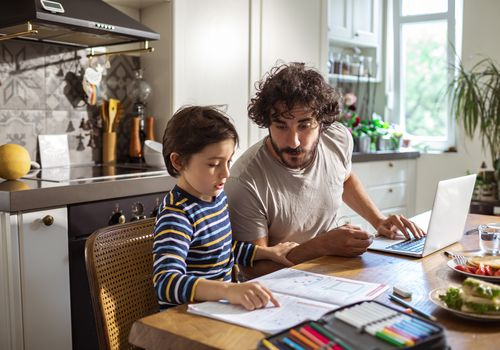 Father helping his son with schoolwork