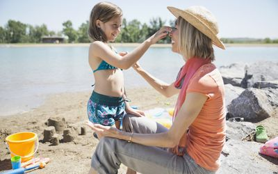 young grandmother at the beach with a granddaughter