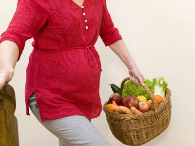 Pregnant woman carrying groceries