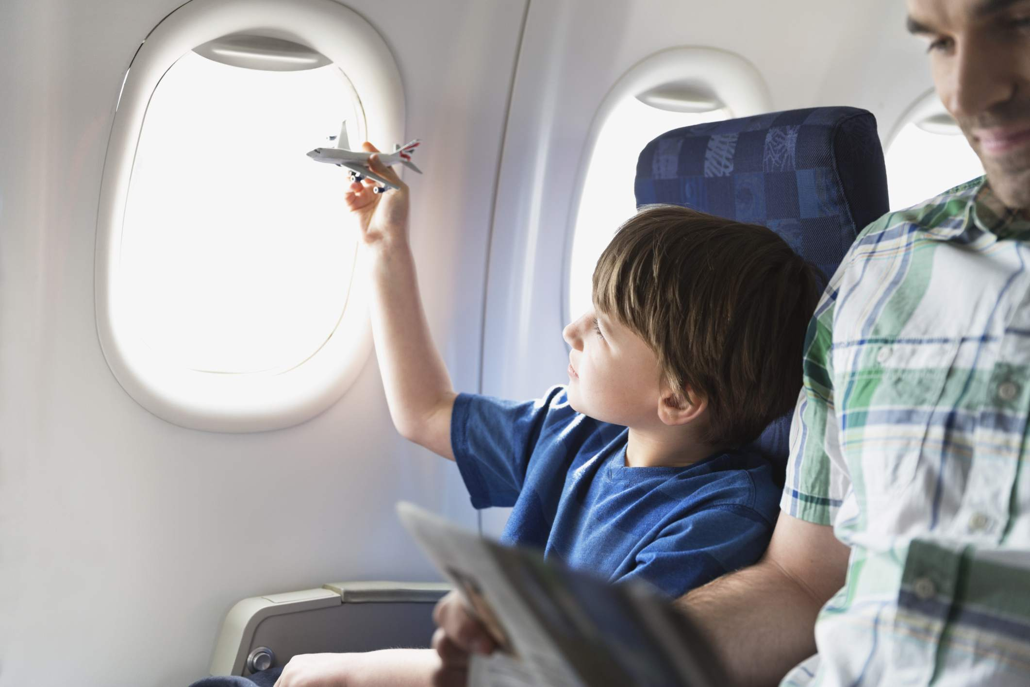 Boy on airplane playing with toy airplane