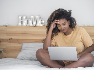 A woman sitting on her bed looking at a fertility forum on her computer