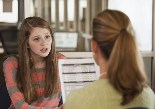 mother holding report card in front of teen girl with upset look on her face