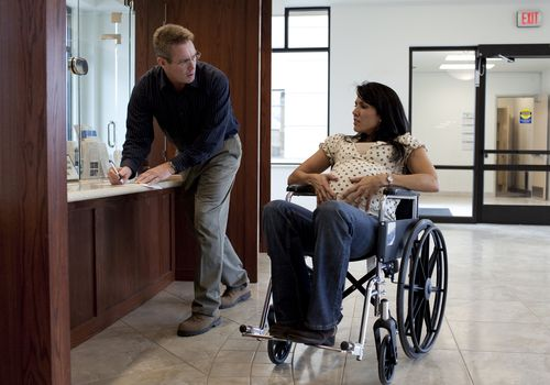 Pregnant woman in wheelchair and man at hospital check-in desk