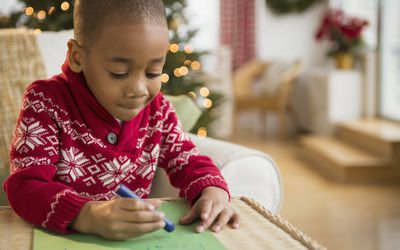 Young boy writing a letter to Santa