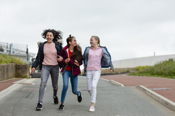 Three cheerful teenage girls arm in arm