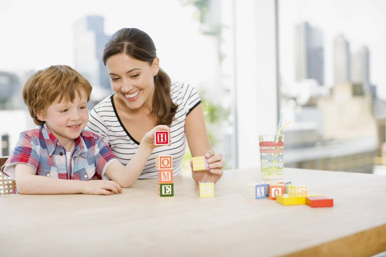A picture of a mom and child playing a learning game with blocks