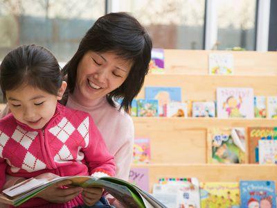 Girl (4-5) sitting on lap of teacher reading book, smiling