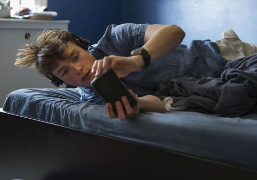 BOY AGED 16 ON BED WITH HEADPHONES AND SMART PHONE