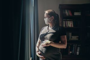 A pregnant person wearing a mask looks out a window